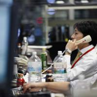 Employees work in the trading room at the Daiwa Securities Group Inc. headquarters in Tokyo on Dec. 1.   BLOOMBERG