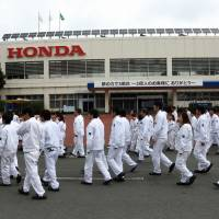 Workers are seen at Honda Motor Co.'s plant in Ozu, Kumamoto Prefecture, in this 2014 file photo. The automaker plans to lift the retirement age by five years to 65. | BLOOMBERG