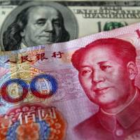 A yuan banknote is displayed next to a U.S. dollar banknote at a money exchange facility inside Taoyuan International Airport in Taipei. | REUTERS