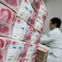 Chinese yuan banknotes sit stacked at the Korea Exchange Bank headquarters in Seoul in July. | BLOOMBERG