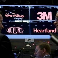 Traders gather at the post where DuPont is traded on the floor of the New York Stock Exchange on Friday. | REUTERS