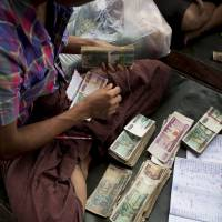 A man counts Myanmar Kyat notes at Thirimingala Market in Yangon on Oct. 12. Experts say it was a long and tough road to open a stock exchange in the country.   BLOOMBERG