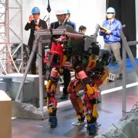 Robot HRP-2 Kai (left) demonstrates walking on a narrow path, while Jaxon shows that it can duck while moving. The humanoids were on display at the International Robot Exhibition 2015 in Tokyo's Koto Ward. Both are designed for work following disasters and were demonstrated at a booth operated by New Energy and Industrial Technology Development Organization. | KAZUAKI NAGATA
