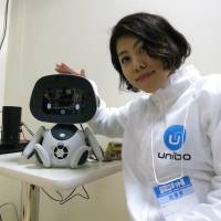 A Unirobot Corp. worker displays the company's Unibo toy during the International Robot Exhibition 2015 in Tokyo's Koto Ward on Wednesday. | KAZUAKI NAGATA