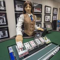 Min, a prototype human-like electronic croupier, deals a card during a demonstration at the headquarters of Paradise Entertainment Ltd. in Macau, China, on Dec. 1. | BLOOMBERG
