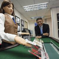 Jay Chun, chairman of Paradise Entertainment Ltd., is photographed with Min, a prototype human-like electronic croupier, at the company's headquarters in Macau, China, on Dec. 1. | BLOOMBERG