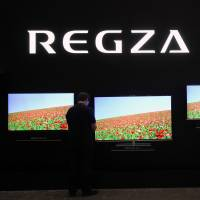 An attendee of CEATEC Japan 2012 looks at Toshiba's Regza 4K LCD televisions.  | BLOOMBERG
