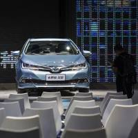 An attendee stands near a Toyota Motor Corp. Corolla hybrid at the International Automobile Exhibition in Guangzhou, China, in November. | BLOOMBERG