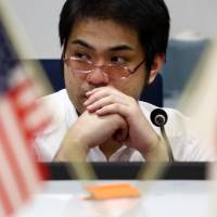 A currency trader is seen at work in the dealing room of the Tokyo Forex Ueda Harlow Ltd. foreign exchange brokerage in Tokyo in December 2014.   BLOOMBERG