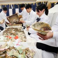 Counting cash: Bankers tally up the donations at Kyoto's Fushimi Inari Grand Shrine following the New Year's holiday period in January. | KYODO