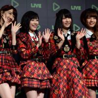 Christmas gift: Japan's girl pop group AKB48 members (from left) Yuki Kashiwagi, Mayu Watanabe, Yui Yokoyama and Rena Kato pose for photographs as Japanese social networking service company Line announces the company's live streaming service for entertainment, artists' performances and their daily lives during a press conference in Tokyo on Thursday. | AFP-JIJI
