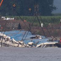 In this June 5 photo, rescuers use cranes to lift the capsized cruise ship Eastern Star on the Yangtze River in Jianli County of southern China's Hubei province, as seen from across the river from Huarong County of Hunan province. | AP