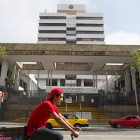 A cyclist pedals past the Jalisco state immigration office, where Ethan Couch and his mother, Tonya, are in custody and waiting for deportation, in Guadalajara, Mexico, Wednesday. | REUTERS