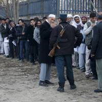 Afghan men line up to apply for passports at a passport department office in Kabul on Nov.29. | REUTERS