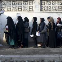 Afghan women wait to apply for passports at a passport department office in Kabul on Nov. 29. | REUTERS