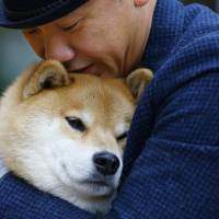 Shinjiro Ono hugs his Shiba Inu Maru at Ueno Park in Tokyo on Dec. 23. This bundle of fun and fur is a 7-year-old Shiba Inu who has been top dog on Instagram for several years. Marutaro has 2.2 million followers on Instagram. | AP