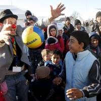 A member of Red Noses Clowndoctors entertains migrants before their departure to Austria at a registration center in Dobova, Slovenia, Sunday. | REUTERS