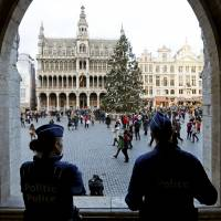Belgian police stand guard Tuesday on Brussels' Grand Place after two people were arrested in Belgium on Sunday and Monday, both suspected of plotting an attack in Brussels on New Year's Eve, federal prosecutors said. | REUTERS
