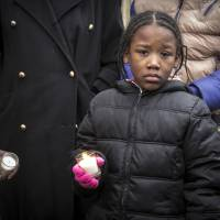 A child holds a candle during a vigil outside Bettie Jones' home on Sunday in Chicago. Jones and Quintonio LeGrier, 19, were killed early Saturday by police responding to a domestic disturbance on the city's West Side, police said. | ASHLEE REZIN / CHICAGO SUN-TIMES VIA AP