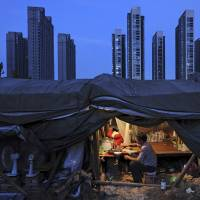A Chinese laborer eats dinner in his shed at a construction site for a residential complex in Hefei, Anhui province, in this file photo. | REUTERS