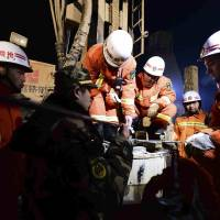 Rescuers try to contact trapped people Monday at a collapsed mine in Pingyi County, east China's Shandong Province. Chinese state media says rescuers have found eight surviving miners who have been trapped for five days by a collapse at a gypsum mine in eastern China.  | GUO XULEI / XINHUA NEWS AGENCY via AP