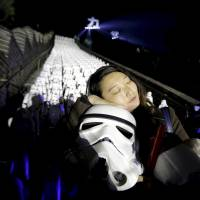 A Star Wars fan holds a stormtrooper helmet during a promotional event at the Great Wall of China on Oct. 20. | REUTERS