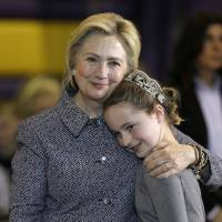 Democratic presidential candidate Hillary Clinton gets a hug from fifth-grader Hannah Tandy during a town hall meeting at Keota High School in Keota, Iowa, on Tuesday. | AP