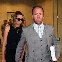 Megaupload executive Finn Batato and his wife, Anastasia, leave court in Auckland on Wednesday. | AFP-JIJI