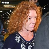 Tonya Couch, center, is taken by authorities to a waiting car after arriving at Los Angeles International Airport on Thursday. | AP