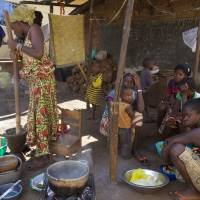 People prepare food at a homestead in Conakry Tuesday. Guinea has been declared free from transmission of Ebola, the World Health Organization said Tuesday, marking a milestone for the West African country where the original Ebola chain of transmission began two years ago leading to the largest epidemic in history. | AP
