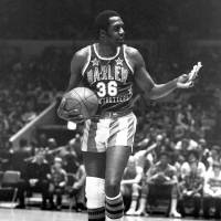 Meadowlark Lemon, of the Harlem Globetrotters basketball team, offers a pretzel to a referee during a 1978 game at New York's Madison Square Garden. | AP