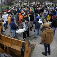 Volunteers form a human chain as they help load sandbags Tuesday in St. Louis. | AP