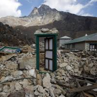 A door of a house that collapsed in an earthquake this year still stands on Nov. 30 in the Sherpa village of Khumjung in Nepal's Solukhumbu district. | REUTERS