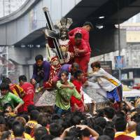 Filipino Catholic devotees jostle to get closer to the image of the Black Nazarene during a thanksgiving procession on New Year's Eve in Manila on Thursday. | AP