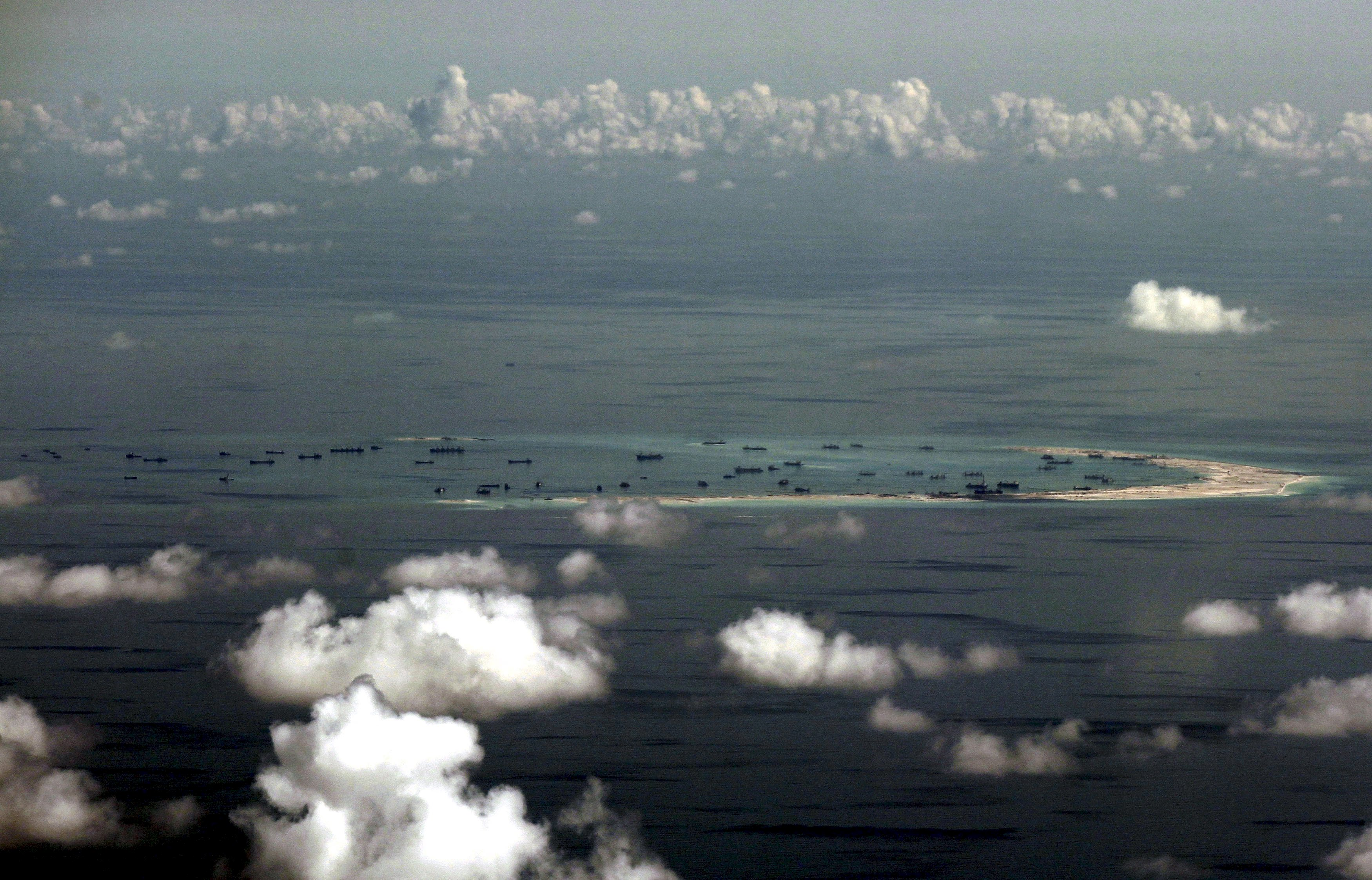The ongoing land reclamation by China on Mischief Reef in the Spratly Islands in the South China Sea, west of Palawan, Philippines, is seen in this aerial photo taken though a glass window of a Philippine military plane in May 2015. | REUTERS