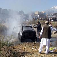 Pakistani firefighters extinguish a fire in a vechile at the site of a bomb explosion at a market in Parachinar, the capital of Kurram tribal district, on Sunday. A bomb hidden in a bag ripped through a crowded bazaar in a mainly Shiite area of Pakistan's northwestern tribal region, killing at least 23 people and wounding more than 30. | AFP-JIJI
