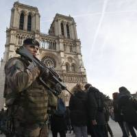 A soldier patrols at the Notre Dame cathedral in Paris, Wednesday. France's defense minister has visited troops on duty ahead of unusually tense New Year's Eve celebrations in Paris after November attacks that left 130 dead and hundreds injured. | AP