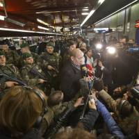 French Foreign Legion members guard France's Defense Minister Jean-Yves Le Drian as he speaks to the media at Auber's metro station in Paris, Wednesday. | AP