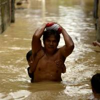 Residents cross a flooded alley in Candaba, Pampanga, north of Manila on Friday. | AFP-JIJI
