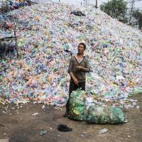 A Chinese laborer sorts plastic bottles for recycling in the Chinese village of Dong Xiao Kou, on the outskirts of Beijing, in September. | AFP-JIJI
