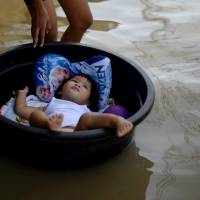 A child lies in a plastic wash basin along a flooded street in Calumpit Bulacan, north of Manila, on Dec. 24. In the southern Philippines, the Christmas period was marred by deadly violence by Muslim separatists. | AFP-JIJI