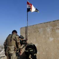 Iraqi soldiers plant a national flag in the government complex in central Ramadi, 70 miles (115 km) west of Baghdad, Monday. | AP