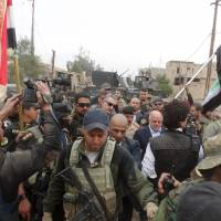 Iraqi Prime Minister Haider al-Abadi walks with his security detail in the city of Ramadi on Tuesday, a day after the army retook the city center from Islamic State, a victory that could help vindicate his strategy for rebuilding the military after stunning defeats in the past 18 months.   REUTERS