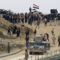 Iraqi security forces gather near a temporary bridge built by the corps of engineers in the Iraqi army south of Ramadi, during a visit by Iraqi Prime Minister Haider al-Abadi on Tuesday, after government forces recaptured the city from the Islamic State group. | AFP-JIJI