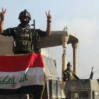 A member of the Iraqi security forces gestures at a government complex in the city of Ramadi Monday. | REUTERS