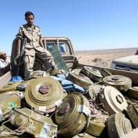 A soldier loyal to Yemen's government stands on the back of a truck transporting land mines left by the Houthi rebels in al-Jadaan area, which was taken by pro-government army from the Houthis, in the country's central province of Marib on Monday. | REUTERS