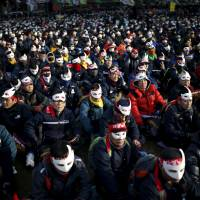 Protesters wearing masks take part in an anti-government rally in central Seoul on Saturday. | REUTERS