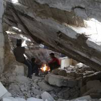Boys warm themselves around a fire at a damaged building where they come to play in the rebel-controlled area of Maaret al-Numan town in Idlib province, Syria, Tuesday. | REUTERS
