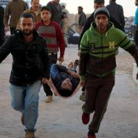 Men carry an injured man on a stretcher at the entrance of a field hospital in the town of Dael, after what activists said were airstrikes carried out by the Russian air force in Sheikh Meskeen near Deraa, Syria, Friday. | REUTERS