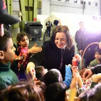 Berlin's Integration Sen. Dilek Kolat gives chocolate to children refugees during her visit of the refugee accomodation at the former Tempelhof airport in Berlin on Saturday. | AFP-JIJI